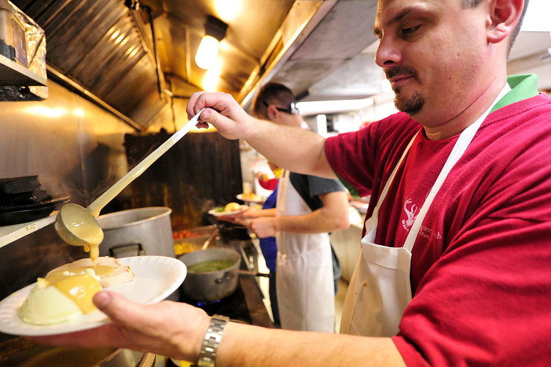 Walt Hester | Trail Gazette<br /> Troy Nelson, owner of the Wapiti Grille ladles gravy onto mashed potatoes on Christmas Day. Nelson had seven volunteers lined up to help serve at the annual free dinner, but 14 volunteers showed up to help.