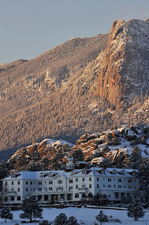 Walt Hester | Trail Gazette<br /> The iconic Stanley Hotel sits snow-covered and shadowed below the blanketed Lumpy Ridge on Thursday. Sunshine and warmer temperatures are expected for the last days of 2011.