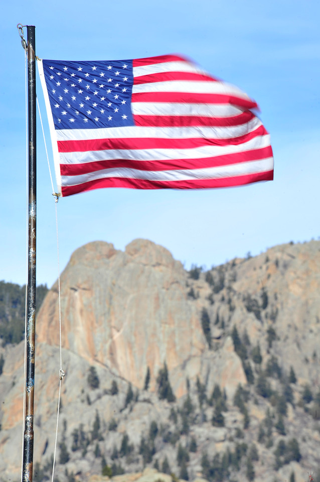 Walt Hester | Trail Gazette<br /> Wednesday's high winds whip the flag at the Estes Park post office. Stiff breezes are expected to continue through the weekend.