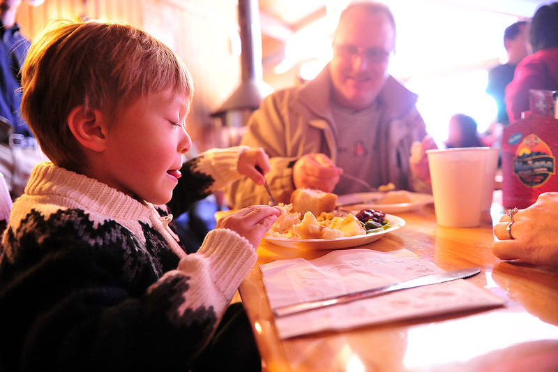 Walt Hester | Trail Gazette<br /> Andrew Altwegg, 5, of Tucson, Ariz. pushes turkey onto his fork at the annual Wapiti Grille free Christmas dinner. Some 50 plates were loaded and served in the first half hour of the event.