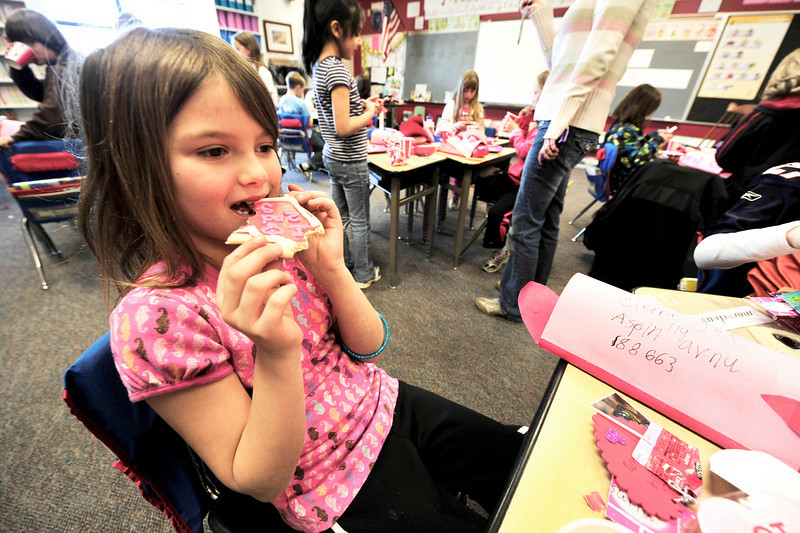 Walt Hester | Trail Gazette<br /> Sierra Jett, 7, enjoys a staple of Valentine's Day, a frosted, heart-shaped cookie, during elementary school parties on Monday.