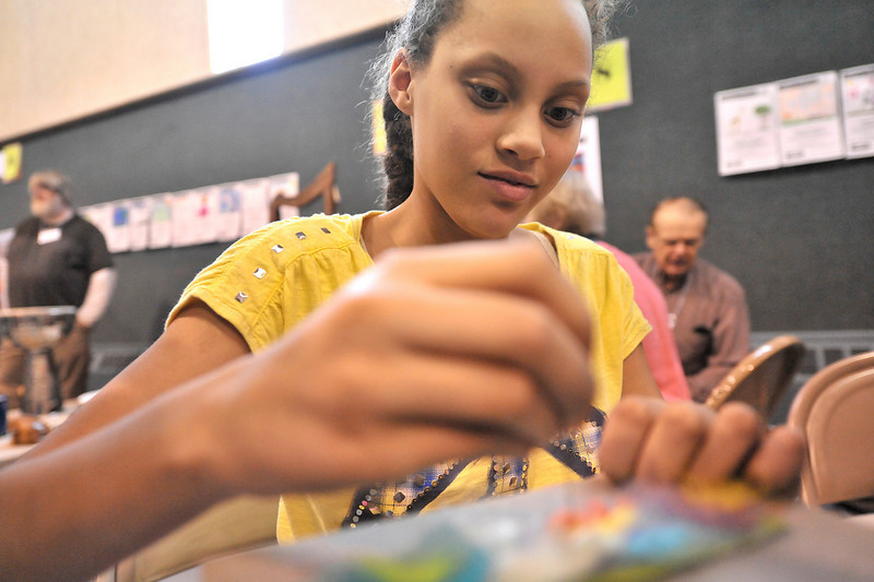 Walt Hester | Trail Gazette<br /> Angel Brown, 11, pokes felt through another piece of fabric to creat a book mark. The Stitchin' Den and several other Estes Park businesses lended a hand to Imagine This.