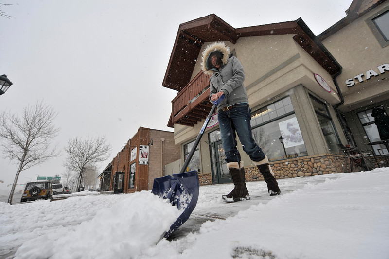 Walt Hester | Trail Gazette<br /> Laura English shovels the sidealk along Elkhorn Avenue as snow begins to fall on Thursday afternoon. Snow continued to fall all day Friday until six to eight inches accumulated in Estes Park.