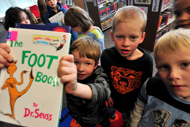 Walt Hester | Trail Gazette<br /> Payton Zelle, 6, holds a favorite book by Dr. Seuss while in the Este Park Middle School library with his class mates Nolan Marske, 7, and Rylan Leonhardt, 6, on Wednesday. Wednesday was the birthday of the beloved childres' author.