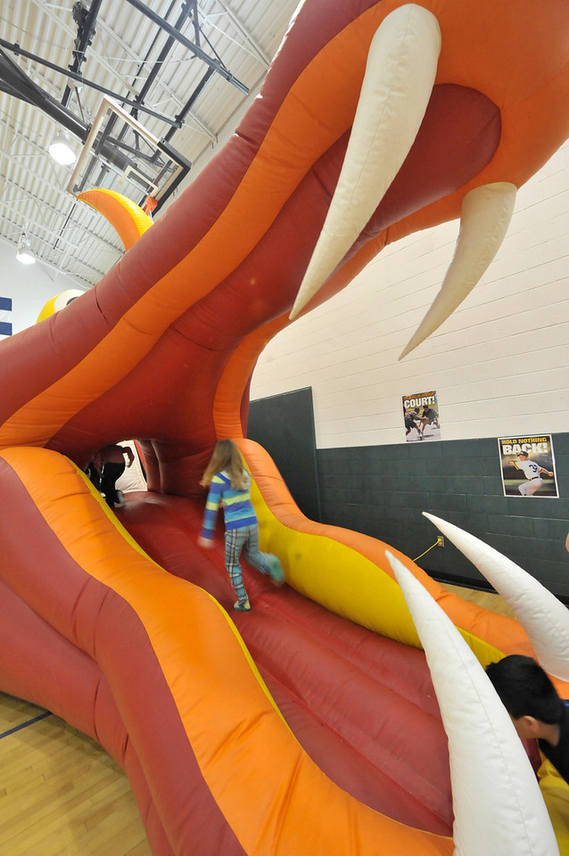 Walt Hester | Trail Gazette<br /> Children at the Estes Park Elementary School Carnival run up a dragons mouth to get to the slide in back on Sunday.