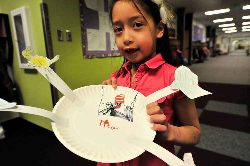 Walt Hester | Trail Gazette<br /> Tita Asuncion, 7, show off her Seuss-themed artwork at the Estes Park Elementary School on Wednesday. Wednesday was the beloved author's 107th birthday.