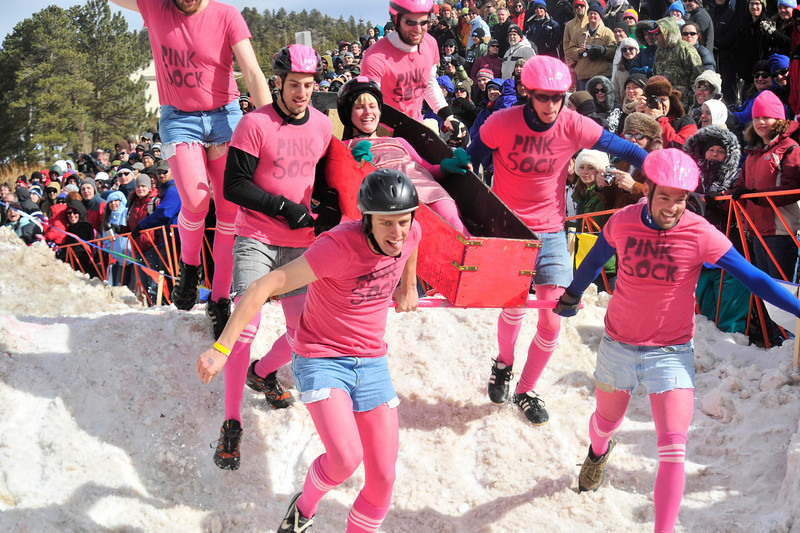 Walt Hester | Trail Gazette<br /> Thousands of visitors jam a hillside in Chipeta Park in Nederland to watch the Coffin Races. Teams carry a coffin of their own making through a frozen obstical course and into a Tuff-Shed.