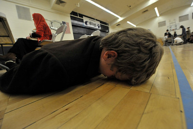 Walt Hester | Trail Gazette Dillon Rodgers, 13, lies face-down on the gym floor during the Estes Park Middle School's Ellis Island day on Wednesday. High school students often order the yonger students to porform tasks or punish arbitrarily to give the younger students a feeling of the sort of lack of fairness and often fear the immigrants who passed through Ellis Island went through.