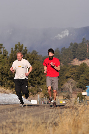 Walt Hester | Trail Gazette<br /> Runners glide across the undulations of Chiefs Head Road into the Saturday morning sun as snow begins to fall behind them in Rocky Mountain National Park. No snow is expected over the weekend in Estes Park.