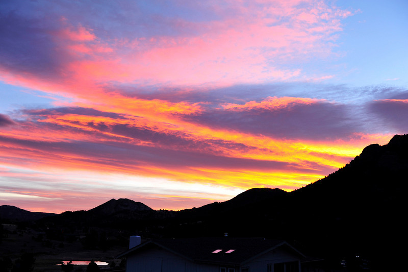 Walt Hester | Trail Gazette<br /> Red, orange, pink and blue greeting early-risers in Estes Park on Saturday. Calm early, winds would again pick up on Saturday afternoon, ushering in snow and cold on Sunday.