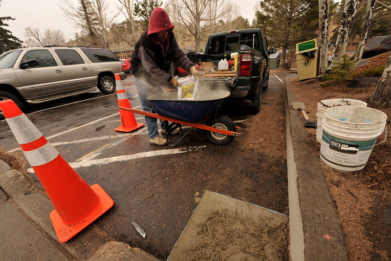 Walt Hester | Trail Gazette<br /> Richard Polley prepares concrete at the Tregent Park parking lot on Wednesday. Polley is installing metal trash cans around town for the Public Works department.