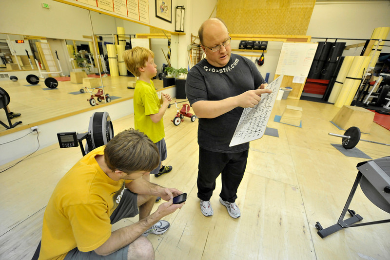 Walt Hester | Trail-Gazette<br /> Trainer Joel York, seated left, and Eric Adams add up the kids scores during Saturday's fund raiser. Between scores and donors, York will receive in the neighborhood of $3,000 to help with his medical bills.
