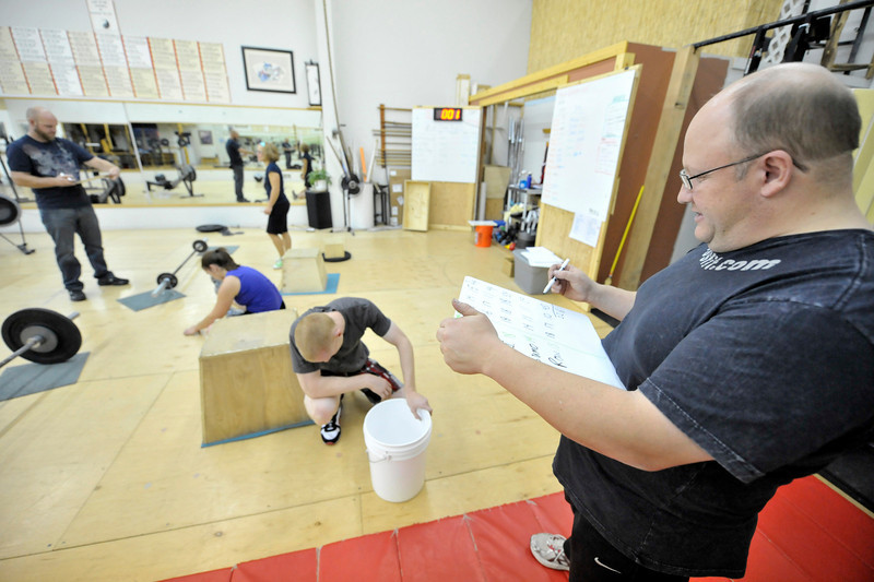 "Walt Hester | Trail-Gazette<br /> Adams adds up scores for Whitney Taylor and Nathanial Romig on Saturday, while the two recover. ""This workout will find your weakness,"" says Adams of the Fight Gone Bad."