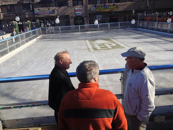 Town officials, including mayor Bill Pinkham, right, discuss the official opening of the town ice rink in downtown Estes Park. The rink will be open as late as mid March.
