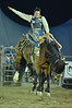 A saddle bronc rider loses his hat but hangs on to his ride on Tuesday night.