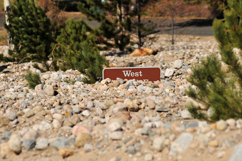 A sign at the Alluvial Fan is barely visible over flood debris on Wednesday. The historic September flood reformed the landscape of the fan, which was formed by the Lawn Lake Flood of 1981.