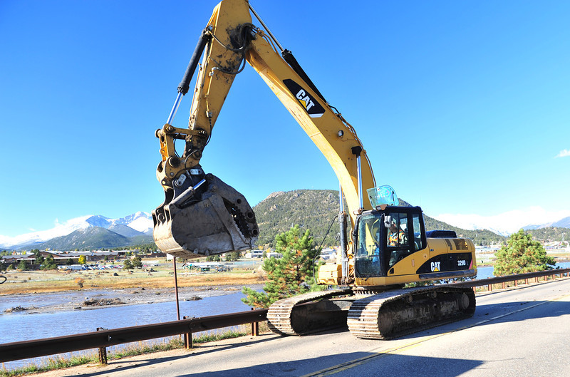 An excavator trundles across the causeway on North St. Vrain Avenue on Wednesday. The equipent was being used to remove flood debris from the lake.