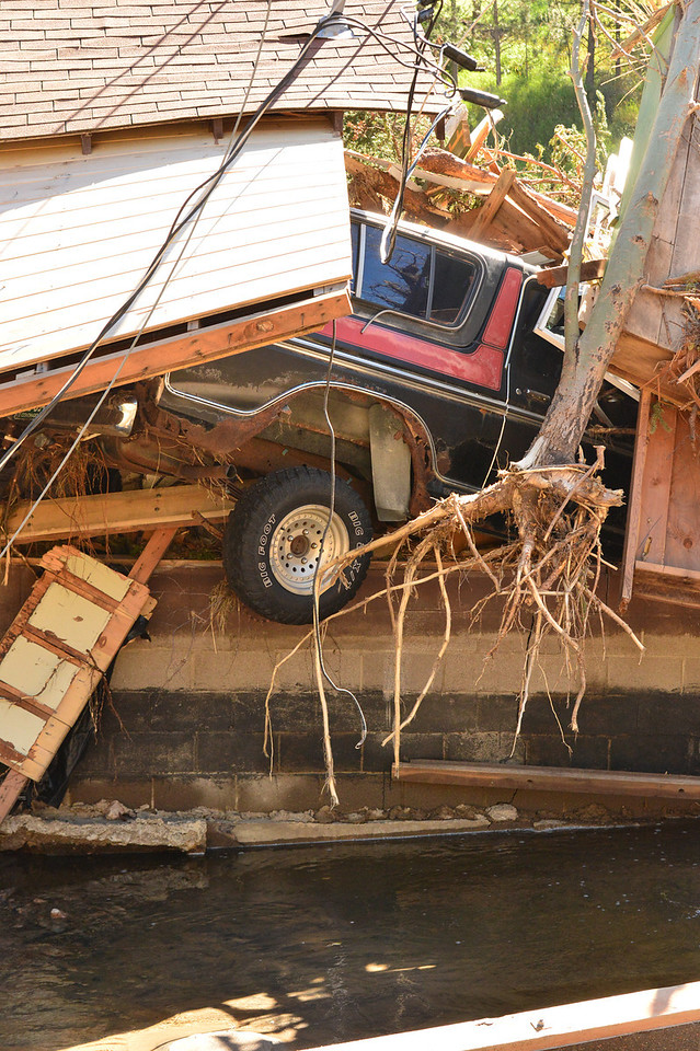 A truck hangs out of the back of the Glen Haven Town Hall. Everything upstream for at least 100 yards was washed into and through the little town hall building.