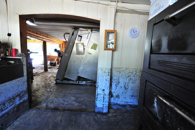 Walls and a walk-in refrigerator tell the flood story in the Glen Haven General Store on Wednesday. Water reached four feet up the walls and hit with such force that it pushed out the bottom of the refrigerator.