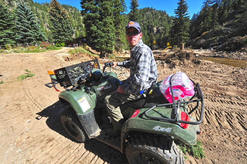 A Glen Haven resident and volunteer firefighter makes his way back to his home on Wednesday. The ATV has become the prefered mode of travel throughout the stricken areas after the September flood.