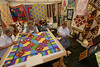 Photo by Walt Hester<br /> Ladies demonstrate 100-year-old quilt-making techniques at the Heritage Festival that are still in.
