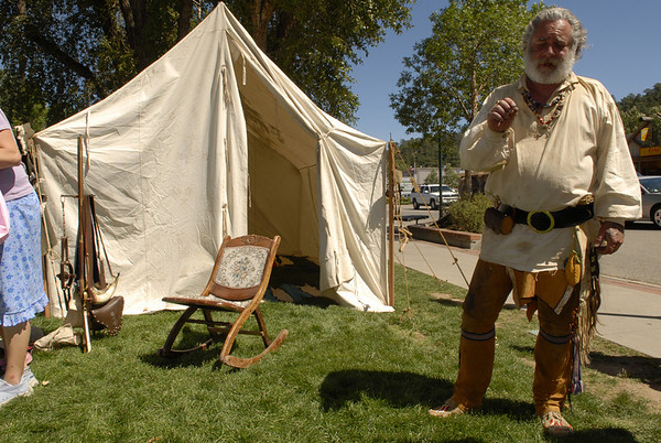 Photo by Walt Hester<br /> A mountain man answers questions from visitors at the Heritage Festival. Mountain men from around the Mountain West and plains will set up tents and stay in Bond Park during the weekend festival