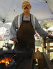Photo by Walt Hester<br /> A blacksmith demonstrates his art and science for passers-by in Bond Park