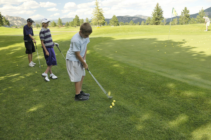 Photo by Walt Hester<br /> Carson Joens and sophomore Jorden Duell watch sophomore Will Casey chip onto the practice green at the public 18-hole course on Wednesday. Boys golf is the first of many fall sports to start practice.