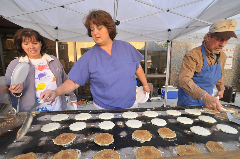 Photo by Walt Hester<br /> Park R3 superintendent Linda Chapman watches school board member Dr. Marie Richardson flip pancakes along with Richard Grunewald at the district's school year kickoff pancake breakfast at Estes Park High School on Tuesday. School begins on Monday, though teachers and administrators have been back to work this week.