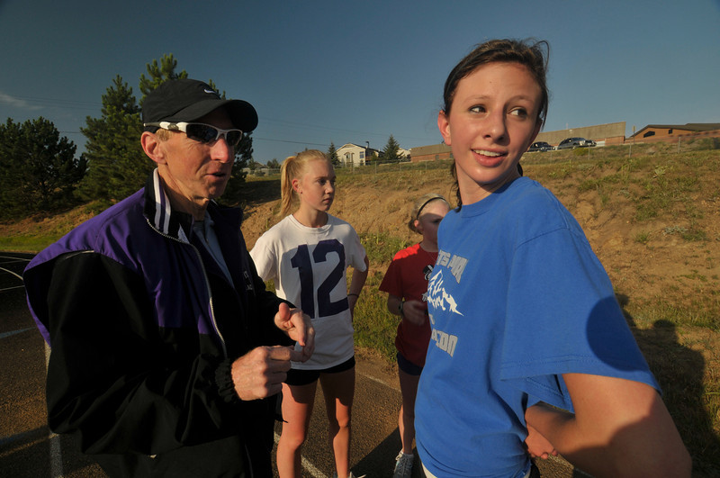 "Photo by Walt Hester<br /> Coach Bill Ruth instructs swimmer-turned-runner Brittany Walters during practice on Tuesday morning. Ruth encourages swimmers to run cross country because of their ""big engines,"" aerobic capacity."