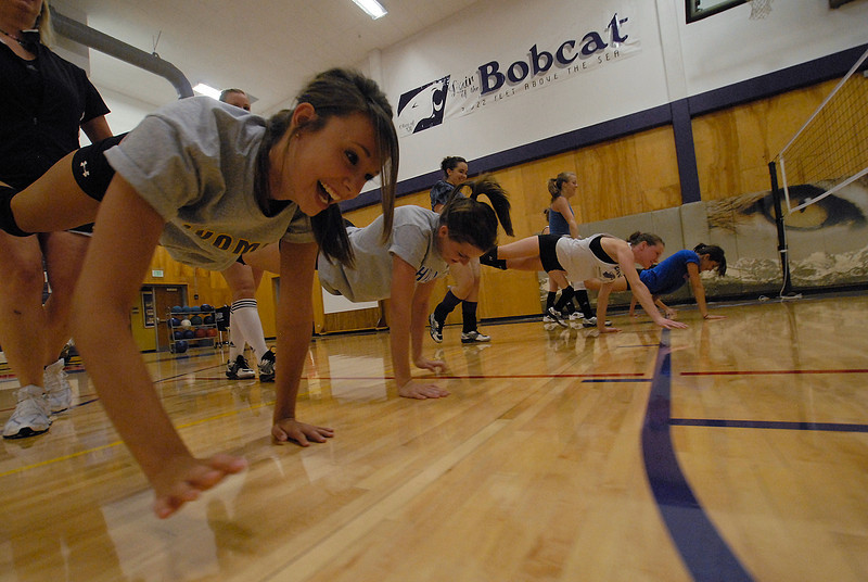Photo by Walt Hester<br /> Kali Holler laughs during upper-body conditioning at volleyball practice on Tuesday. The Ladycat's face off with Peak to Peak at home on Tuesday, Sept. 8.