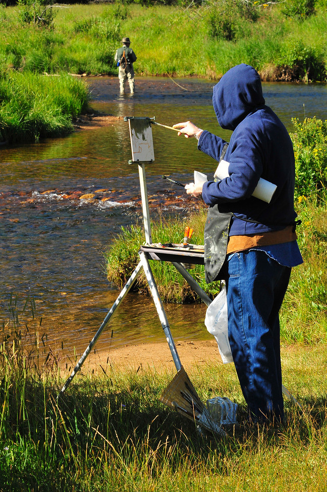 Photo by Walt Hester<br /> Gerri Bradford of Longmont paints along the Big Thompson River in Moraine Park as Gene Cope, also from Longmont, fly fishes on Wednesday morning.