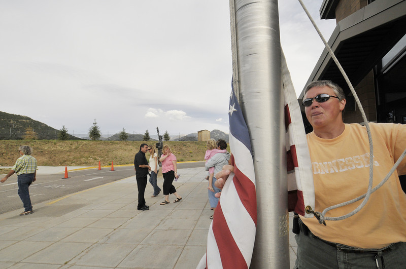 """Photo by Walt Hester<br /> """"Miss Amy"""" Sawlaw raises the flag to start another school year at the Estes Park Elementary School on Monday."""