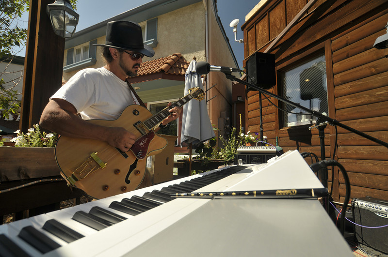 Photo by Walt Hester<br /> One-man digital band Peter Gibbs soaks up the sun while performing on Riverside Plaza on Thursday. Warm sunshine coaxed plenty of people outside throughout the weekend in Estes Park.