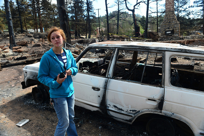 Walt Hester   Trail Gazette<br /> Emily Franklin clutches her fire scanner while walking through the remains of her family's home on Columbine Drive on Tuesday. Franklin gave neighbors direction while trying to save the home in which she grew up.