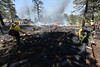 Walt Hester | Trail Gazette<br /> A ground crew from Black Hills National Forest break up a woodpile and dowse smoldering spots on Saturday. Firefighters from as far away as Boulder and Loveland joined the fight of the Woodland Heights Fire.