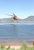 One of the helicopters being used to fight the Woodland Heights Fire west of downtown Estes Park Saturday, June 23, uses a snorkle to refill its tanks from Lake Estes.