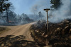 Walt Hester | Trail Gazette<br /> The properties around Columbine and Narcissus smolder on Saturday. The worst loss of property centerd around the intersection in the Woodland Heights Fire.