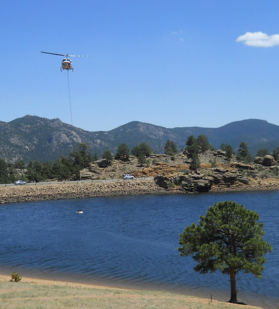 A helicopter-mounted water bucket splashes in the water of Marys Lake Saturday afternoon while being refilled to fight the Woodland Heights Fire on the western edge of Estes Park.
