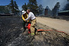Walt Hester | Trail Gazette<br /> Firefighter work to open a hydrant on Columbine Drive on Saturday. Firefighters work furiously to save the homes they could and help stop the spread of the Woodland Heights Fire.