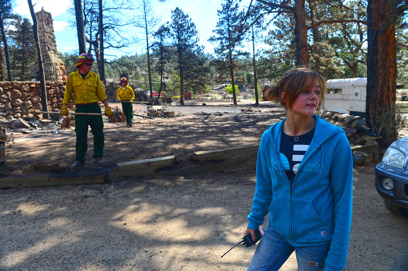 Walt Hester | Trail Gazette<br /> Emily Franklin, right, looks over her family's property on Tuesday as firefighters walk through checking for hot spots. Residents of the Woodland Heights Fire were allowed to return to their property on Tuesday.