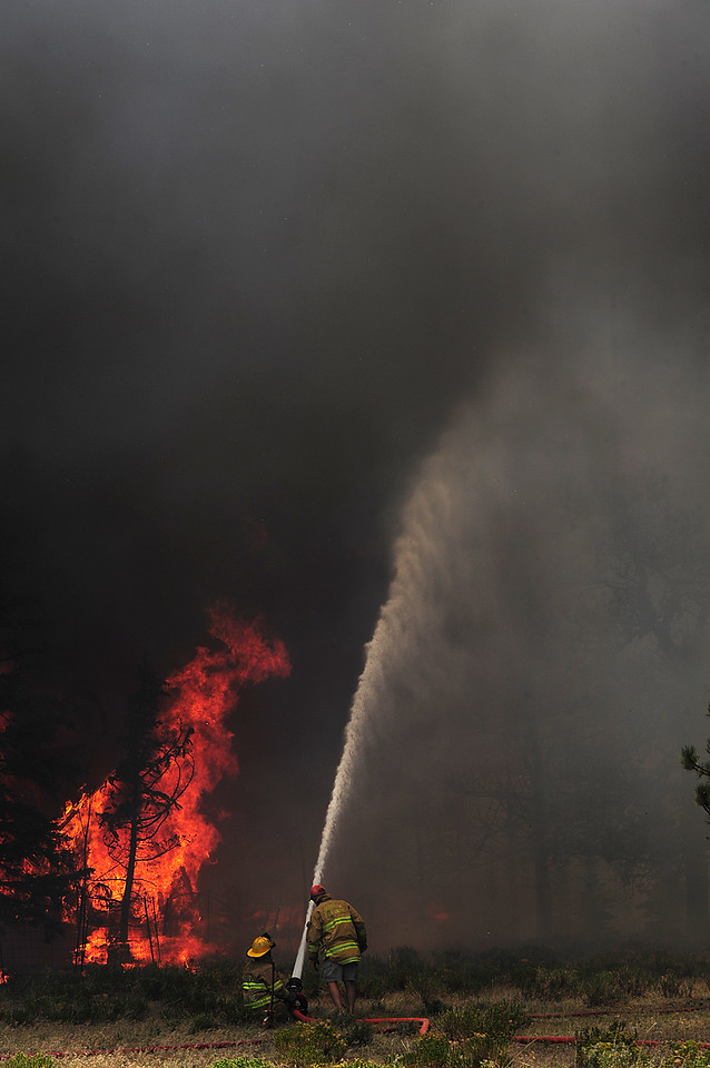 Walt Hester | Trail Gazette<br /> Firefighters lob water into a wall of smoke and flame early Saturday afternoon. Firefighters from several agencies and communities faught heat and high winds all Saturday afternoon to save what they could and keep the Woodland Heights Fire from advancing into surrounding subdivisions.