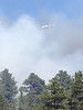 Helicopters dump water on a blaze that has grown from a few structures into several homes and surrounding trees. Winds are making containment extremely difficult.