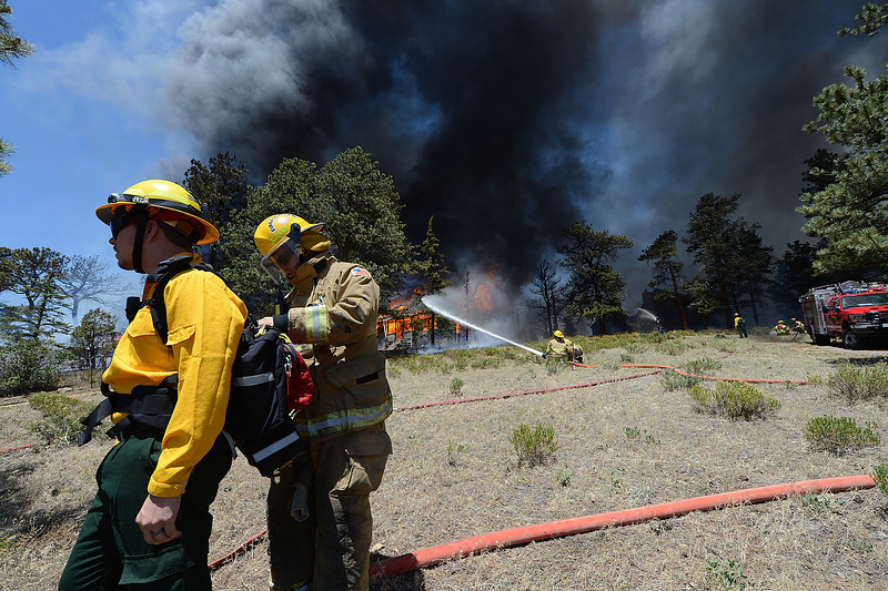 Walt Hester | Trail Gazette<br /> Firefighters from different agencies help each other while fighting the Woodland Heights Fire on Saturday. At least ten agencies contributed ground crews in the battle against Saturday's fire.