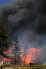 Walt Hester | Trail Gazette<br /> Flames and smoke billow from the Woodland Heights Fire on Saturday. In less than an hour, wind drove the fire through several homes and heavy timber.