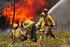 Walt Hester | Trail Gazette<br /> Firefighters defend homes and fight flames as well as heat and high winds on Saturday. The Woodland Heights Fire took 21 structures and blackened 20 acres before multiple agencies could bring the blaze under control.