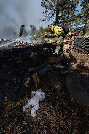 Walt Hester | Trail Gazette<br /> An abandon toy lays near firefighters as they break up a wood pile and spray smoldering remains of a house in the Woodland Heights Fire on Saturday. Many residents had little notice as the fast-moving fire engulfed parts of the High Drive neighborhood.