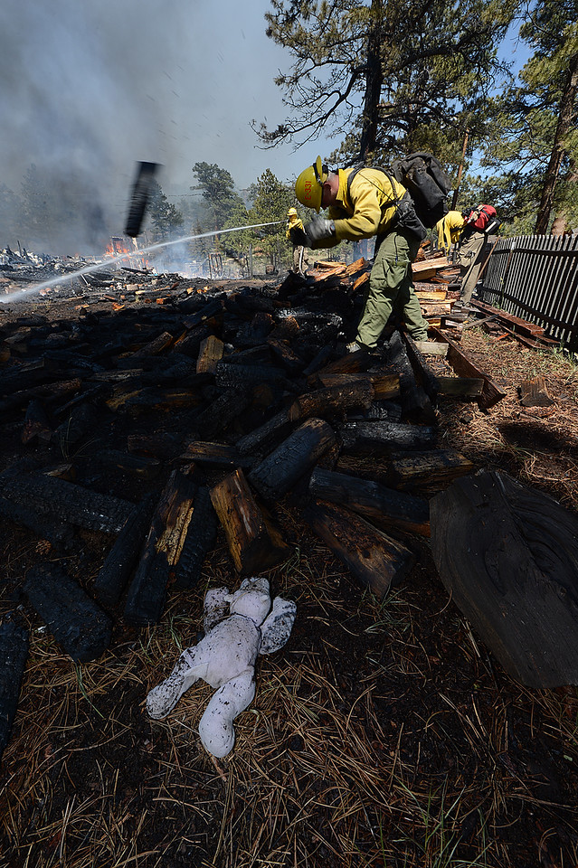 Walt Hester   Trail Gazette<br /> An abandon toy lays near firefighters as they break up a wood pile and spray smoldering remains of a house in the Woodland Heights Fire on Saturday. Many residents had little notice as the fast-moving fire engulfed parts of the High Drive neighborhood.
