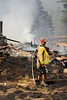 Walt Hester | Trail Gazette<br /> Louiseville firefighter James Bage looks for hotspots in the remains of homes in the Woodland Heights Fire on Saturday. Several firefighters in town for vacation answered the call when the fire erupted.