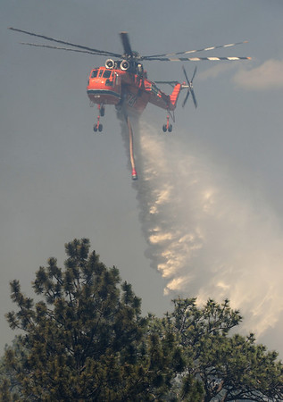 Walt Hester | Trail Gazette<br /> A type-one helicopter drops nearly 3,000 gallons of water on the Woodland Heights Fire. At least 16 structure burned in the Saturday afternoon fire.